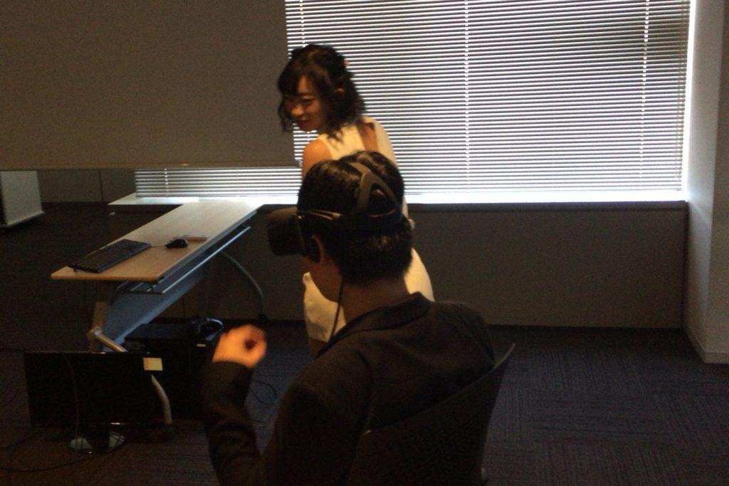 VRデート体験が終わりヘッドセットを取り外そうとする記者